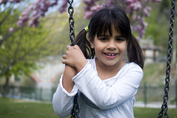 Young girl sitting on swing, smiling, portrait