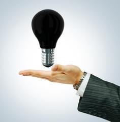 Black light bulb in businessman's hand