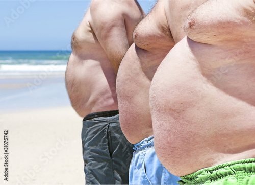 Leinwanddruck Bild Close up of three obese fat men of the beach