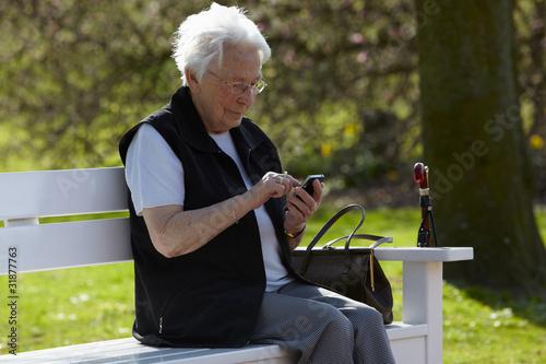 Nette alte Dame mit Telefon sitzend auf Bank 2