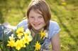 Junges Mädchen geniesst die Blumen im Garten