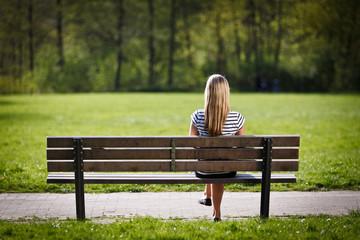 frau sitzt auf einer parkbank