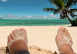 Relaxing feet on beach. Tropical sea, sky background.