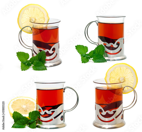 Tea in a glass holder and a sprig of lemon balm