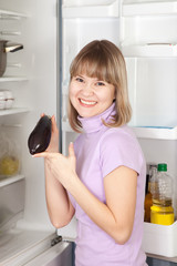 woman taking  egg-plant from refrigerator