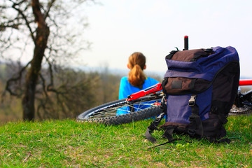 Backpack, bicycle and girl on nature
