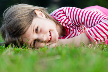 a beautiful young girl lays in a field
