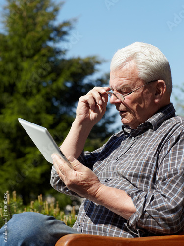 Old handsome man using touchpad e-book reader