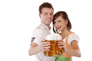 Bayer und Frau im Dirndl stossen mit Oktoberfest Maßkrügen an