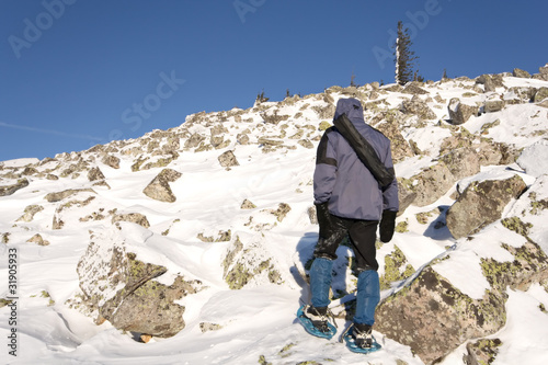 Climber in snowshoes (snow shoes) walking at the mountain slope