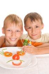 boys holding a plate with vegetables