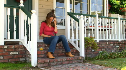 Young woman talking on cell phone sitting on front porch