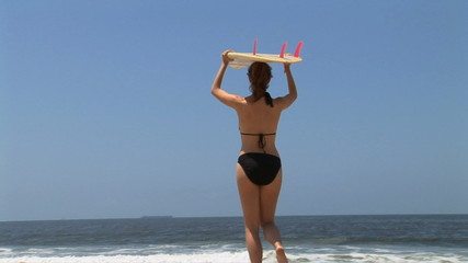 Young woman walking to ocean with surf board on head