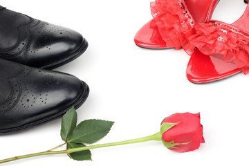 red womens shoes and black mens shoes with a red rose
