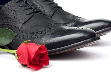 A pair of black mens shoes and a rose