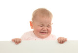 Crying baby girl holding an empty white board
