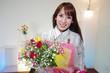 花束を持っている笑顔の女性