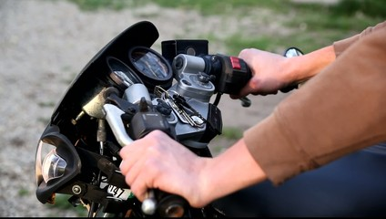 Close-up hands revving a motorcycle