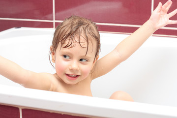 Cute three-year-old girl looking out of a bath and smiling