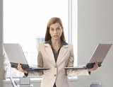 Desperate businesswoman with two laptops poster