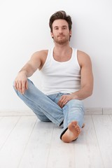 Handsome man sitting on floor by wall