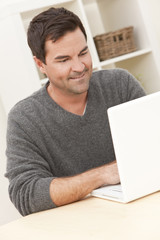 Man Using Laptop Computer At Home