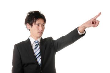指を指すスーツの男性