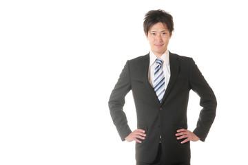 腰に手を当てるスーツの男性