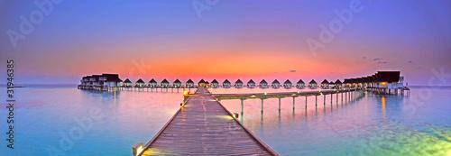 Leinwanddruck Bild Maldives bungalows sunset panorama