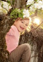 Mädchen sitzt im Apfelbaum und freut sich
