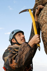 The climber hammers in hook into rock