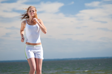 Sport woman running on beach