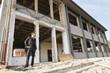 Mann auf der Baustelle vor entkernter Fassade