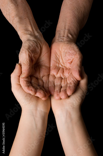 Hands of the old woman on a black background