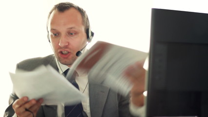 Angry businessman with headset and documents screaming