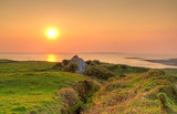 Irish cottage house near ocean at sunset