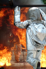 firefighter with fire retardant suit moving through the flames