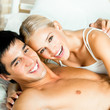 Young attractive happy smiling couple at bedroom