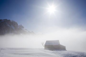 Nebel und Hütte in den Alpen