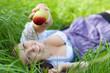 Frau in der Wiese hält Apfel entgegen