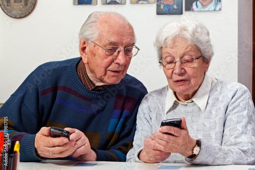 Leinwandbild Motiv senior couple with smartphones