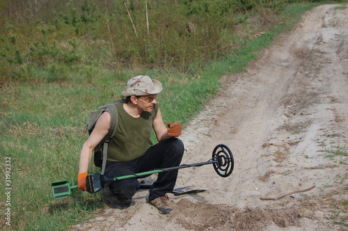 Man with metal detector on the battlefield of WW2