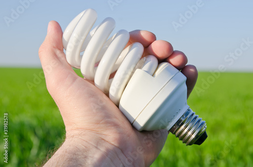 energy saving lamp in hand over green field