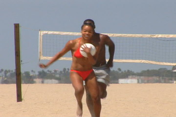 Young African-American couple playing volleyball at the beach