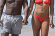 Young African American couple holding hands and walking