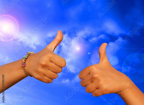 Woman's hand close-up shows a gesture ok against the blue sky