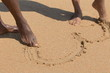 Young African American couple drawing heart in sand with feet