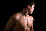 Atractive muscular young man against black background