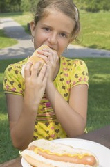 Young Girl Eating A Hot Dog Outdoors