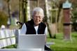 Nette alte Dame mit Laptop auf Bank 31